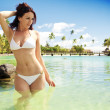 Young woman in white bikini standing next to beach — Stock Photo #4729039