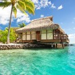 Over water bungalow with steps into  lagoon - Stock Photo