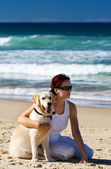Young female sitting on a beach with a dog — Stock Photo