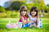 Two young smiling girls hugging in the grass — Stock Photo