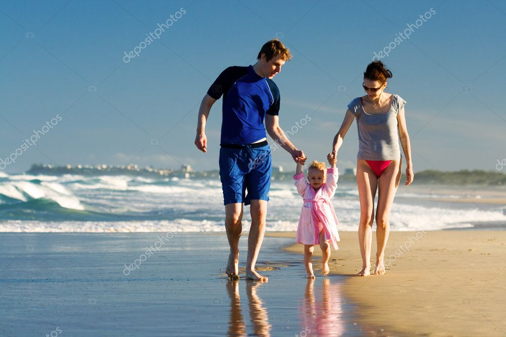 Young family walking on the beach  Stock Photo #4728440