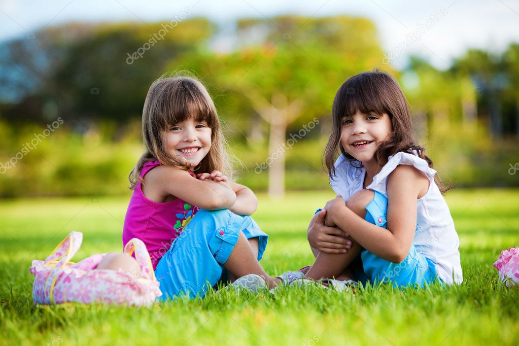 Two young smiling girls sitting in the grean grass — Stock Photo #4729017