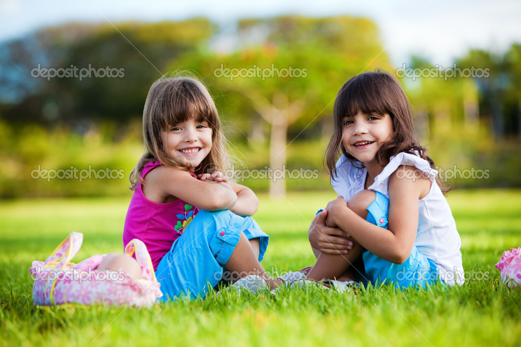 Two young smiling girls sitting in the grean grass  Stock Photo #4729017