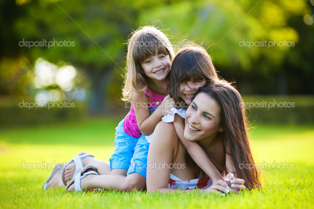 Young mother and two daughters playing in grass  Stock Photo #4729020