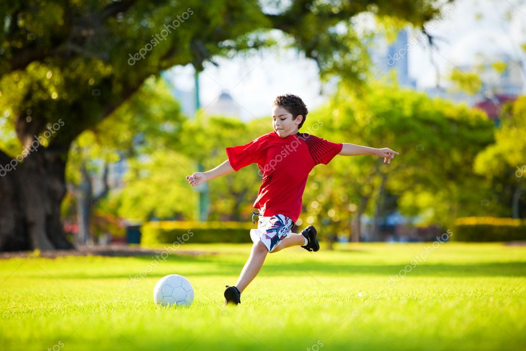 Young excited boy kicking ball in the grass outdoors — Stock Photo #4729022