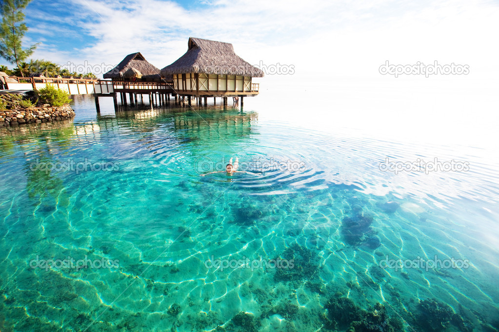 Young woman in white bikini swimming in a coral lagoon — Stock Photo #4729032