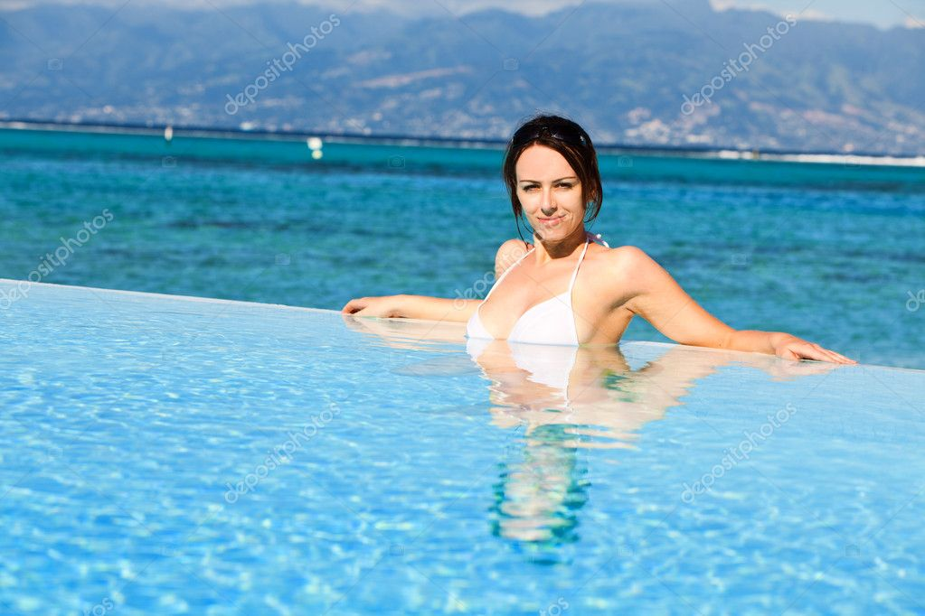 Young woman in white bikini resting at the edge of pool — Stock Photo #4729034