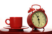 Traditional red alarm clock with a red cup — Stock Photo
