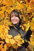 Beautiful girl among yellow autumn leaves — Stock Photo
