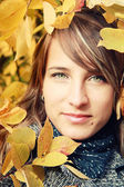 Beautiful girl among autumn leaves — Stock Photo