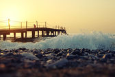 Beautiful sunrise on the sea through the pier, pebles and waves — Stock Photo