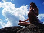 Girl meditating on a mountaintop — Stock Photo