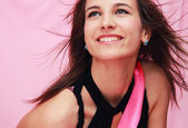 Beautiful young smiling girl on a pink background — Stock Photo