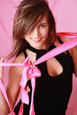 Sexy smiling girl with bow on a pink background — Stock Photo