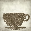 Textured old paper background with cup made of coffee beans — Stok fotoğraf