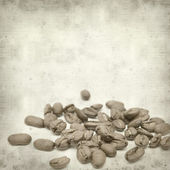 Textured old paper background with scattered coffee beans — Stock Photo