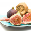 Fresh figs; Prosciutto and broken pieces of granary bread on square blue pl — Stock Photo #4719103