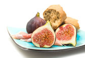 Fresh figs; Prosciutto and broken pieces of granary bread on square blue pl — Stock Photo