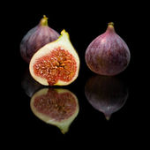Ripe purple fig fruits isolated on black background, with reflection — Stock Photo