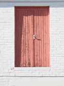 Pink door in white brick wall, high above the ground — Stock Photo