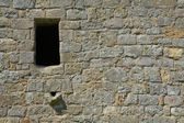 Old stone wall with window and drain — Stock Photo
