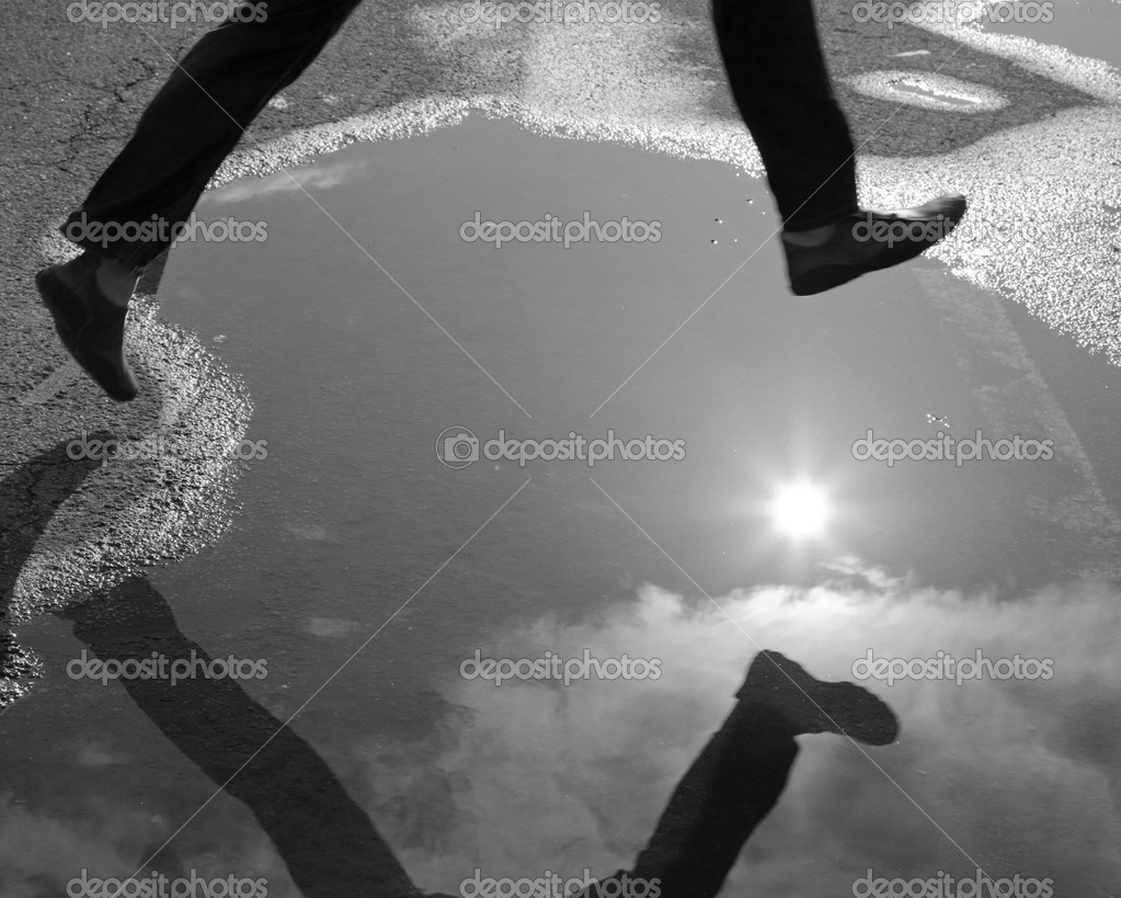 Jumping over a pool of water, some motion blur, monochrome, black and white, legs. male. long. jump. reflection, sun, beautiful, surface, road, rain, urban — Stok fotoğraf #4949170
