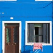 Burano island in lagoon of Venice; brightly-colored house; washing - Stock Photo