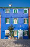 Burano island in lagoon of Venice; brightly-colored blue house — Stock Photo