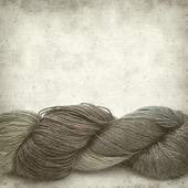 Textured old paper background with hand-dyed yarn skein — Stock Photo