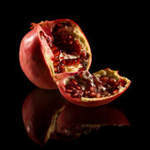 Pomegranate; broken fruit isolated on black reflective surface; — Stock Photo
