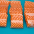 Raw fresh trout portions on blue plastic chopping board; — Stock Photo