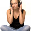 Foto de Stock  : Girl sitting to feel sound through headphones