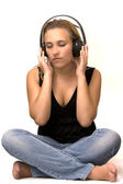 Girl sitting to feel the sound through headphones — Stockfoto