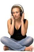 Niña sentada para sentir el sonido a través de auriculares — Foto de Stock
