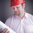 Young attractive engineer with blueprints — Stock Photo