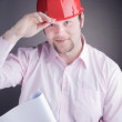 Stock Photo: Young Engineer with blueprints raises his hat