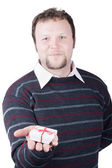 Young man holding valentine gift in his hand. He is giving it so — Stock Photo