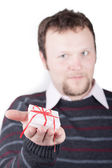 Young man holding valentine gift in his hand — Stock Photo