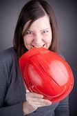 Portret kobiety młody inżynier jedzenie czerwonych kasków ochronnych, patrząc na — Zdjęcie stockowe