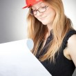 Young woman in helmet with blueprint — Stock Photo #4799240