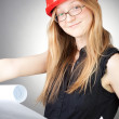 Stock Photo: Young woman in helmet with blueprint