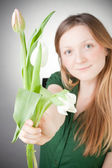 Young blonde girl with tulips, with grey background — Stock Photo
