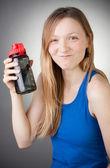 在她手中的一瓶水穿蓝色衬衫的年轻女子 — 图库照片