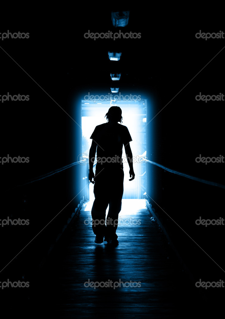 Young Man walking out of the light  Stock Photo #5215867