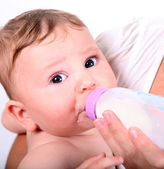 A baby eating milk from the bottle — Stock Photo