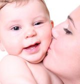 Happy young mother kissing a baby — Stock Photo