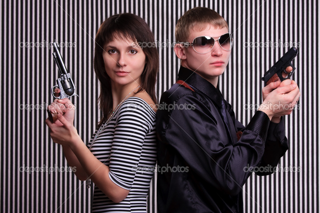 Young couple holding guns over stripe background — Stock Photo #5242407