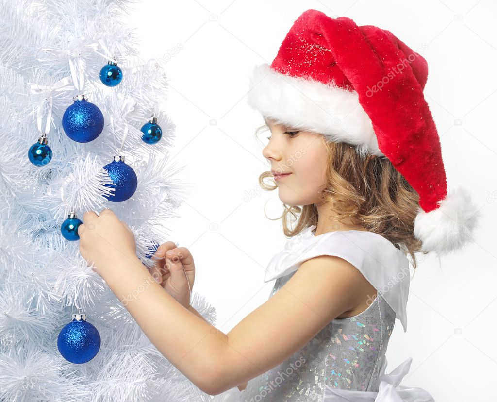 Pretty girl in red santa's hat decorating christmas tree — Stock Photo #4466819