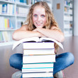 Royalty-Free Stock Photo: Pretty female college student in a library (shallow DOF; color t