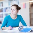 Pretty young college student in a library (shallow DOF; color to — Stock Photo